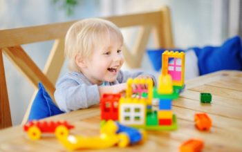 little-boy-playing-with-colorful-plastic-blocks-kindergarten-home_107864-1323